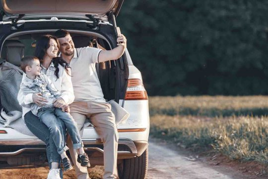 Family in a forest. People by the car. Sunset background.